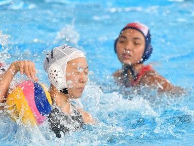 Pemain Jepang, Marina Tokumoto (tengah) memperjuangkan bola saat melawan Indonesia dalam babak penyisihan polo air putri Grup A Asian Games 2018 di Jakarta, Kamis (16/8). Indonesia kalah 4-15. (PETER PARKS/AFP)