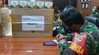 Anggota Kodim 0508/Depok menyiapkan paket obat untuk warga yang melakukan isolasi mandiri di Kota Depok. (Liputan6.com/Dicky Agung Prihanto)