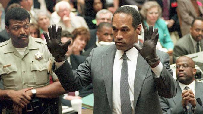 Mantan atlet American Football, O. J. Simpson, mencoba sarung tangan, yang merupakan bukti pembunuhan, di persidangan pada 21 Juni 1995. (AFP/Vince Bucci)