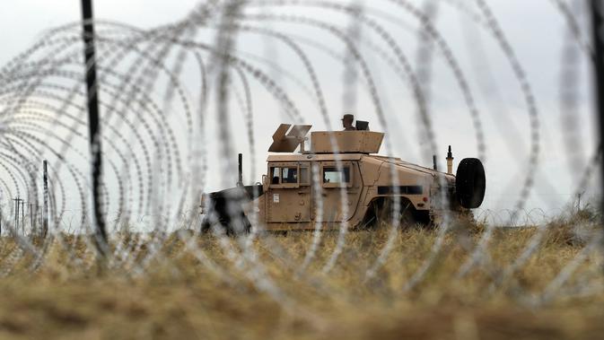 Tentara AS mengawasi sekitar dari balik barikade kawat duri dekat Jembatan Internasional AS-Meksiko di Donna, Texas,Minggu (4/11). Sebagian besar dari para imigran mengatakan berencana mengajukan permohonan suaka di AS. (AP Photo/Eric Gay)