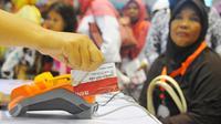 KKS saat digunakan di Cibubur, Jakarta, Kamis (23/2). Keluarga kurang mampu yang menerima Bantuan Pangan Non Tunai dapat langsung menggunakan KKS untuk berbelanja bahan pokok di e-warung di lingkungan mereka. (Liputan6.com/Angga Yunair)