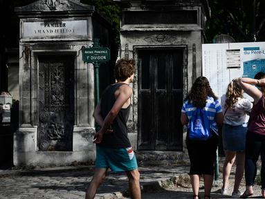 Turis melihat peta pemakaman Pere Lachaise sebelum memulai kunjungan mereka di Paris (22/7/2019). Pemakaman Père adalah salah satu pemakaman terbesar di Paris (luasnya sekitar 44 hektar 110 acre). (AFP Photo/Philippe Lopez)