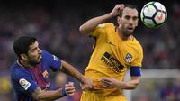 Bek Atletico Madrid, Diego Godin, duel udara dengan striker Barcelona, Luis Suarez, pada laga La Liga Spanyol di Stadion Camp Nou, Barcelona, Minggu (4/3/2018). Barcelona menang 1-0 atas Atletico. (AFP/Lluis Gene)