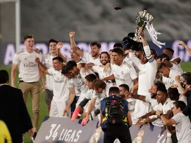 Para pemain Real Madrid mengangkat piala saat merayakan kemenangan La Liga musim 2019/20 usai menaklukkan Villarreal di Estadio Alfredo Di Stefano, Kamis (16/7/2020). Real Madrid memastikan diri menjadi juara Liga Spanyol setelah mengalahkan Villarreal 2-1. (AP Photo/Bernat Armangue)