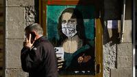 Seorang pria melewati poster seniman Italia TVBOY bergambar Mona Lisa karya Leonardo da Vinci mengenakan masker dan memegang smartphone di Barcelona, Selasa (18/2/2020). Instalasi muncul setelah Mobile World Congress (MWC) 2020 batal digelar karena wabah virus corona yang mencekam. (PAU BARRENA/AFP)