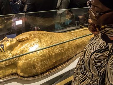 Seorang wanita memperhatikan peti mati emas mumi Nedjemankh yang dipajang di Museum Nasional Peradaban Mesir, Kairo, Selasa (1/10/2019). Nedjemankh merupakan seorang imam di zaman Ptolemeus, sekitar 2.000 tahun lalu. (Khaled DESOUKI/AFP)