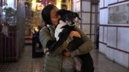 Seorang wanita mencium anjing peliharaannya di dalam gereja San Francisco sebelum pemberkatan hewan di Lima, Peru pada Minggu (6/10/2019). Pemberkatan hewan ini untuk menghormati Santo Fransiskus yang dikenal sebagai santo pelindung bagi binatang dan lingkungan hidup. (AP/Martin Mejia)