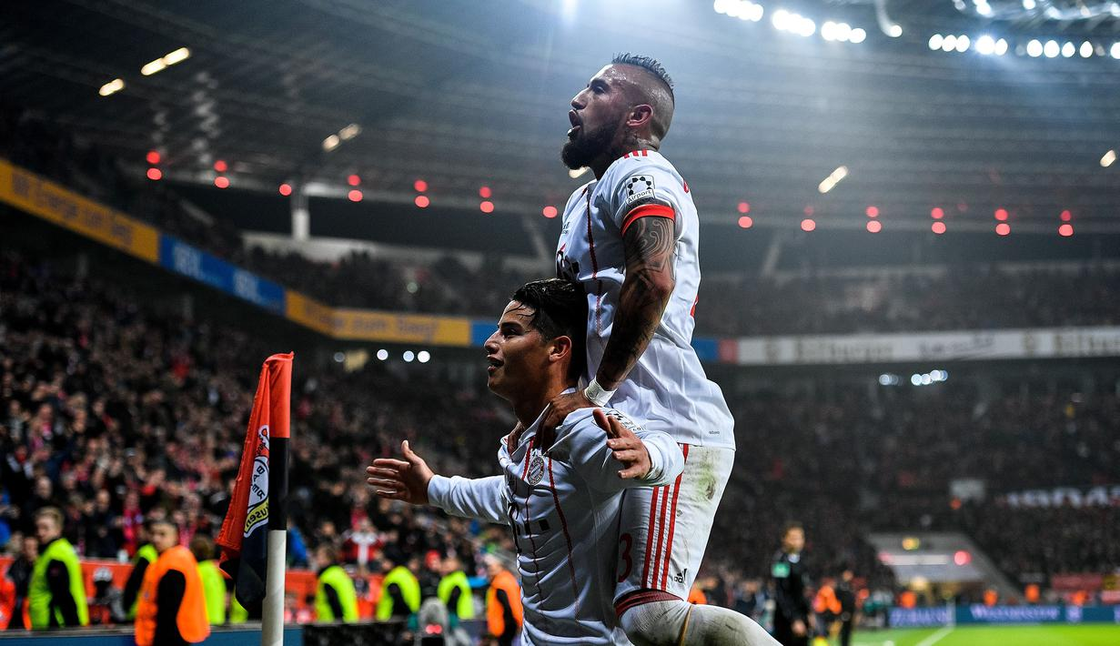 Pemain Bayern Munchen,  James Rodriguez merayakan gol bersama rekannya Arturo Vidal (kanan) saat melawan Bayer Laverkusen pada lanjutan Budesliga di Bay Arena, Laverkusen, (12/1/2018). Bayern Munchen menang 3-1. (AFP/Sascha Schuermann)