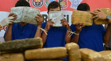 Para tersangka memperlihatkan paket ganja kering saat rilis kasus di Banda Aceh, Aceh, Kamis (23/5/2019). Satresnarkoba Polresta Banda Aceh mengamankan satu ton paket ganja, tiga tersangka dan satu unit truk tronton saat akan membawa narkotika ke Jakarta. (CHAIDEER MAHYUDDIN/AFP)