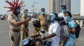 Inspektur polisi Rajesh Babu mengenakan helm berbentuk virus corona saat mengimbau pengendara motor selama lockdown di pos pemeriksaan di Chennai, India, Sabtu (28/3/2020). Cara ini bertujuan agar warga menerapkan social distancing dan tetap berada di rumah selama pandemi Covid-19. (Arun SANKAR/AFP)