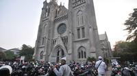 Umat muslim yang akan menunaikan salat Idul Adha di Masjid Istiqlal memarkirkan kendaraan mereka di halaman Gereja Katedral, Jakarta, Minggu (11/8/2019). Untuk membantu jemaah melaksanakan ibadah, Katedral menyediakan lahan parkirnya dan mengundurkan waktu ibadah Misa. (merdeka.com/Iqbal S Nugroho)
