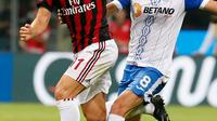 Penyerang AC Milan, Fabio Borini berusaha membawa bola dari kawalan pemain U Craiova, Alexandru Mateiu saat bertanding di leg kedua babak 3 Liga Europa di San Siro, Milan, (3/8). AC Milan sukses menang 2-0 atas Craiova. (AP Photo/Antonio Calanni)