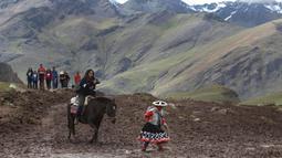 Seorang turis wanita menunggang kuda saat berwisata di Gunung Pelangi di Pitumarca, Peru (2/4). Rainbow Mountain atau Gunung Pelangi terbentuk sekitar 24 juta tahun lalu, akibat gempa tektonik. (AP Photo/Martin Mejia)