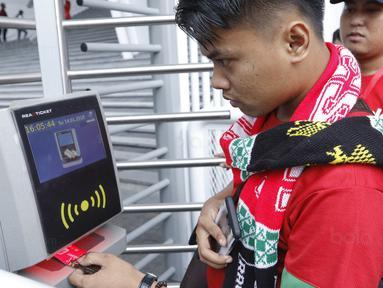 Seorang suporter menempelkan tiket ke mesin barcode saat memasuki SUGBK, Senayan, Jakarta, Minggu (14/1/2018). Fasilitas baru tersebut untuk meningkatkan keamananan, kenyamanan serta kedisiplinan suporter. (Bola.com/M Iqbal Ichsan)