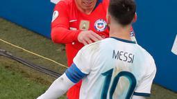 Penyerang Argentina, Lionel Messi berseteru dengan gelandang Chile, Gary Medel selama perebutan posisi ketiga Copa America 2019 di Arena Corinthians, Brasil (6/7/2019). Insiden tersebut berawal dari Messi yang mendorong Medel dari belakang di lini pertahanan Chile. (AP Photo/Nelson Antoine)