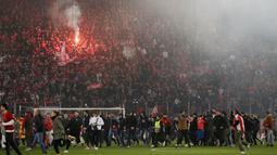 Para suporter Olympiakos turun ke lapangan merayakan kemenangan atas AC Milan pada laga Europa di Stadion Georgios Karaiskakis, Athena, Kamis (13/12). Olympiakos menang 3-1 atas AC Milan. (AP/Thanassis Stavrakis)