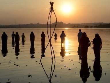 Umat Hindu India memanjatkan doa pada matahari pada festival Chhath di tepi Danau Hussain Sagar di Hyderabad, Selasa (17/11). Dalam festival tersebut, sejumlah umat Hindu berdoa saat matahari terbit dan tenggelam. (AFP PHOTO/NOAH Seelam)