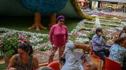 Pengunjung foto di depan merak raksasa selama Festival Bunga di Pusat Perbelanjaan Santa Fe di Medellin, Kolombia (3/8). Merak yang terbuat dari 182.000 bunga ini memiliki panjang 12 meter (40 kaki). (AFP Photo/Joaquin Sarmiento)