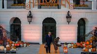 Presiden AS, Donald Trump dan ibu negara Melania Trump membagikan permen kepada anak-anak selama acara trick-or-treat Halloween di South Lawn, Gedung Putih, Senin (28/10/2019). Dalam acara ini anak-anak mengenakan kostum Halloween, sedangkan Donald dan Melania tetap tampil formal. (AP/Alex Brandon)