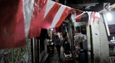 Warga berjalan di Gang Venus, Kelurahan Jembatan Besi, Kecamatan Tambora, Jakarta, Kamis (5/9/2019). Warga Gang Venus harus menggunakan listrik selama 24 jam penuh akibat minimnya cahaya matahari yang masuk ke kawasan mereka. (merdeka.com/Iqbal Nugroho)