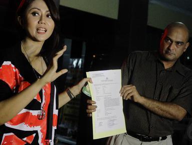Pedangdut Aida Saksia (kiri) dan pengacaranya, Salim Chozie mendatangi Polres Jakarta Selatan pada Minggu (16/11/2014). (Liputan6.com/Faizal Fanani)