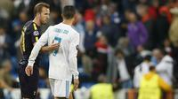 Bintang Real Madrid, Cristiano Ronaldo, saling sapa dengan striker Tottenham, Harry Kane, usai laga Liga Champions di Stadion Santiago Bernabeu, Madrid, Selasa (17/10/2017). Kedua klub bermain imbang 1-1. (AP/Fransisco Seco)