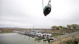 Sejumlah pekerja memindahkan perahu layar ke Great Salt Lake, Utah (6/4). Setelah badai musim dingin menaikan tingkat air danau perahu layar ini akan beroperasi kembali. (AP Photo / Rick Bowmer)