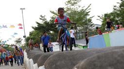 Seorang anak bermain sepeda di area Skate Park RPTRA Kalijodo, Jakarta, Sabtu (15/6/2019). Menjelang sore hari, anak-anak berdatangan menghabiskan waktu dengan bermain di area RPTRA Kalijodo. (Liputan6.com/Helmi Fithriansyah)