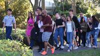 Sejumlah siswa dievakuasi ketika terjadi  penembakan massal sekolah menengah atas Marjory Stoneman Douglas di Parkland, Florida, Rabu (14/2). Insiden itu melukai sejumlah orang dan membuat ratusan murid berlarian ke jalanan. (Michele Eve Sandberg/AFP)