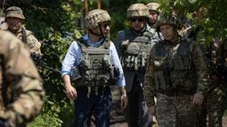 Presiden Ukraina Volodymyr Zelensky saat mengunjungi garis depan medan pertempuran dengan separatis pro-Rusia di Lugansk, Senin (27/5/2019). Zelenskiy mengenakan pakaian sipil, namun juga memakai helm militer dan rompi anti-peluru. (STR/UKRAINE PRESIDENTIAL PRESS SERVICE/AFP)