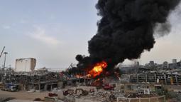 Petugas pemadam kebakaran berupaya memadamkan api yang membakar gudang-gudang di Pelabuhan Beirut, Lebanon, Kamis (10/9/2020). Tentara Lebanon mengatakan kobaran api berkobar dari gudang penyimpanan minyak dan ban di area Bebas Pajak pelabuhan. (AP Photo/Hussein Malla)