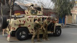 Tentara Afghanistan bersiap siaga di dekat sebuah kantor amal Inggris Save the Children saat terjadi serangan yang sedang berlangsung di Jalalabad, Afghanistan (24/1). Serangan tersebut sedikitnya melukai 11 orang. (AFP Photo/Noorullah Shirzada)