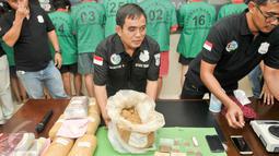 Polres Metro Jakarta Barat merilis penangkapan sepuluh tersangka pengedar narkoba di Jakarta, Senin (30/1). Dari penangkapan tersebut, petugas menyita barang bukti sabu 7,2 kg, tembakau gorilla 1,8kg dan 600 butir happy. (Liputan6.com/Yoppy Renato)