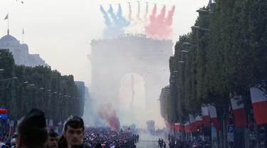 Peswat tempur melepaskan asap berwarna bendera Prancis menyambut kedatangan Les Bleus di Arch of Triumph, Paris, (16/7/2018). Parade tersebut adalah bagian dari perayaan Prancis meraih trofi Piala Dunia 2018. (AFP/Francois Guillot)