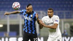 Gelandang Inter Milan, Arturo Vidal, duel udara pemain Borussia Moenchangladbach, Alassane Plea, pada laga Liga Champions di Stadion Giuseppe Meazza, Kamis (22/10/2020). Kedua tim bermain imbang 2-2. (AP/Luca Bruno)