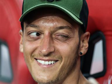 Gelandang Arsenal, Mesut Ozil mengedipkan mata sambil tersenyum ke rekan satu timnya di bangku cadangan selama pertandingan ICC 2018 melawan Atletico Madrid, Singapura (26/7). Arsenal kalah 3-1 setelah bermain 1-1 di waktu normal. (AP Photo/Yong Teck Lim)