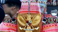 Seorang pria memegang burung Garuda Pancasila di mobil bercorak Ulos Mandailing yang akan digunakan acara ngunduh mantu Kahiyang-Bobby di Medan, Senin (20/11). (Liputan6.com/JohanTallo)