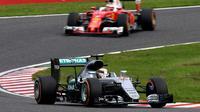 Pebalap Mercedes, Lewis Hamilton, mengungguli pebalap Ferrari, Sebastian Vettel, dalam balapan F1 GP Jepang di Sirkuit Suzuka, Jepang, Minggu (9/10/2016). (AFP/Toshifumi Kitamura)