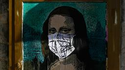 Poster seniman Italia TVBOY yang menggambarkan Mona Lisa karya Leonardo da Vinci mengenakan masker dan memegang smartphone di jalan Barcelona, Selasa (18/2/2020). Instalasi muncul setelah Mobile World Congress (MWC) 2020 batal digelar lantaran wabah virus corona yang mencekam. (PAU BARRENA/AFP)