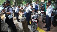 Petugas Dishub menertibkan sepeda motor yang parkir di sepanjang trotoar kawasan Kebon Sirih, Jakarta, Rabu (18/1). Puluhan motor diamankan serta digembosi dalam penertiban tersebut karena menutupi jalur pedestrian. (Liputan6.com/Immaniel Antonius)