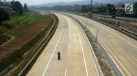 Pekerja melintasi ruas Tol Bogor-Ciawi-Sukabumi (Bocimi) seksi 1 di Ciawi, Bogor, Jawa Barat, Senin (4/6). Presiden Joko Widodo atau Jokowi menargetkan proyek pembangunan Tol Bocimi seksi 1 dapat beroperasi pada Juli 2018. (Merdeka.com/Arie Basuki)