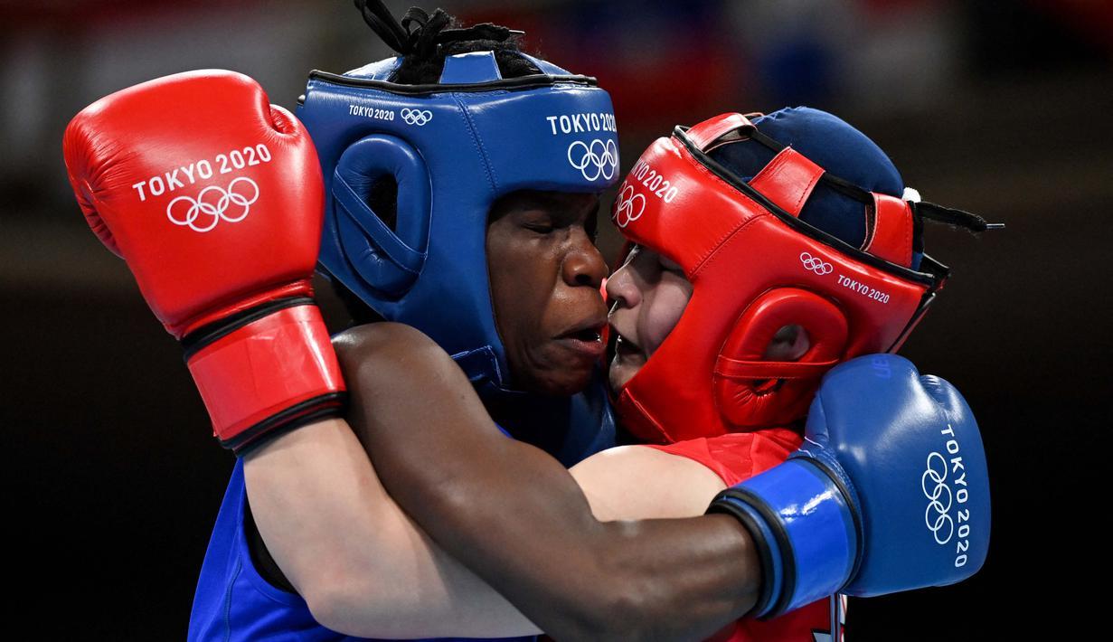 Petinju asal Jepang Tsukimi Namiki (kanan) bertarung dengan Catherine Nanziri asal Uganda dalam pertandingan tinju kelas terbang putri pada Olimpiade Tokyo 2020 di Kokugikan Arena, Tokyo, Minggu (25/7/2021). (Foto: AFP/Various Source/Luis Robayo)