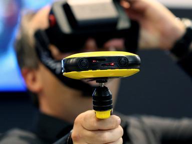 Seorang jurnalis mencoba kamera video Vuze 3D 360 di booth Vuze saat berlangsungnya Pameran Photokina di Cologne, Jerman, (20/9). Pameran ini berlangsung 20-25 September 2016. (REUTERS/Fabrizio Bensch)
