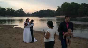 Gislaine Pereira de Araujo berpose untuk foto untuk album pernikahan bersama suaminya Ronilson de Araujo Souza dengan latar belakang hutan hujan Amazon di pantai sungai Jamanxim, di Novo Progresso, Brasil (2/9/2019). (AP Photo/Leo Correa)