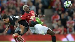 Gelandang Manchester United. Paul Pogba, berebut bola dengan bek Southampton, Jose Fonte. Pertandingan ini merupakan laga perdana Paul Pogba setelah kembali berseragam Setan Merah. (AFP/Oli Scarff)