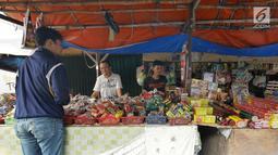 Pedagang melayani pembeli petasan di pasar gembrong, Jakarta, Senin (11/6). Imbas meledakanya pabrik petasan di tanggerang beberapa waktu lalu, harga petasan dan kembang api naik saat menjelang Lebaran 2018. (Liputan6.com/Herman Zakharia)