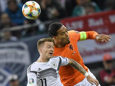 Bek Belanda, Virgil Van Dijk berebut bola udara dengan gelandang Jerman, Marco Reus selama pertandingan grup C  kualifikasi Euro 2020 di Hamburg, Jerman (6/9/2019). Belanda menang telak 4-2 atas Jerman. (AP Photo/Martin Meissner)