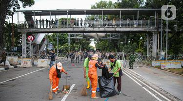 Petugas kebersihan membersihkan sampah sisa pendemo usai unjuk rasa buruh di kawasan Patung Kuda, Jakarta, Kamis (22/10/2020). Sebelumnya, buruh dari berbagai elemen berunjuk rasa menolak pengesahan Omnibus Law UU Cipta Kerja. (Liputan6.com/Faizal Fanani)