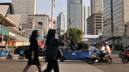 Pejalan kaki melintasi coretan yang dibuat buruh di zebra cross kawasan Sarinah, Jakarta, Selasa (1/5). Jejak vandalisme tersebut antara lain coretan berisi kata-kata kritis buruh dan poster di berbagai fasilitas umum. (Merdeka.com/ Iqbal S. Nugroho)