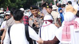 Polisi mengatur arus masuk massa aksi unjuk rasa di depan Kedubes AS, Jakarta, Minggu (10/12). Ribuan massa berkumpul memprotes keputusan Presiden Trump yang mengakui Yerusalem jadi Ibu Kota Israel. (Liputan6.com/Helmi Fithriansyah)